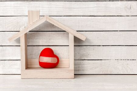 Wood Home Shaped with pain heart and bandage on white wood over white wood background.