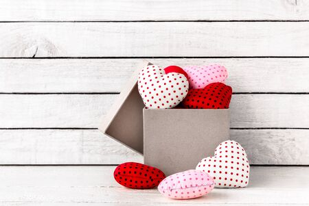 Many Red Heart Shaped with brown gift box over white wood background