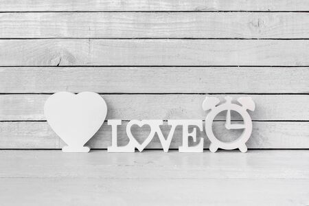 White Heart Shaped with Love Alphabet and Clock Shaped on white wood over white wood background Standard-Bild