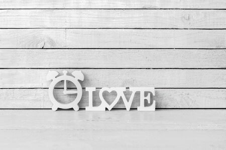 Clock Shaped with Love Alphabet on white wood over white wood background Standard-Bild