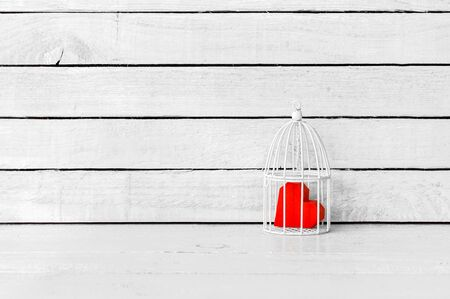 Red Heart Paper Shaped was imprison in cage over white wood background