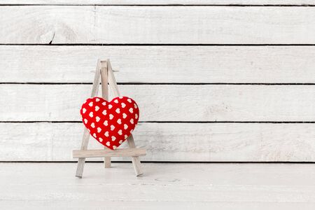 Heart frabic with wood art stand on white wood Background