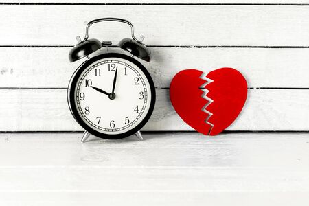 Brokend Heart with alarm clock over white wood background Standard-Bild
