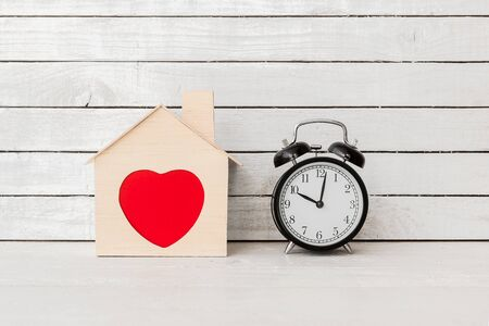 Wood Home Shaped with red heart and alarm clock on white wood over white wood background. Standard-Bild