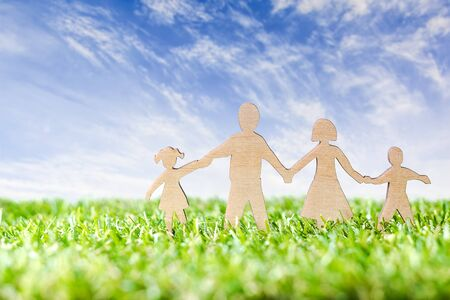 Wood Family Shaped on green grass over beautiful sky.  Green Family Concept. Standard-Bild
