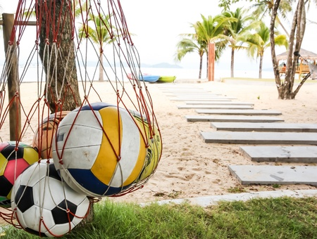 Popular activity in summer is playing sport on the beach such as volleyball and football photo