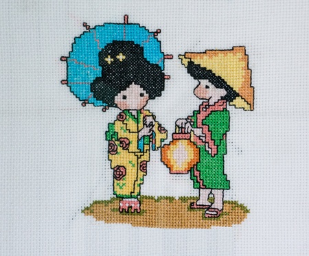 Cross stitch picture of Japanese boy and girl in national dress