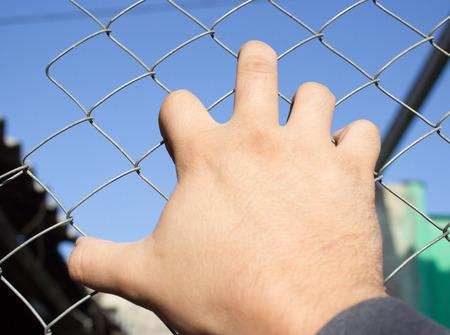 Hand on an iron grid Standard-Bild - 109388821