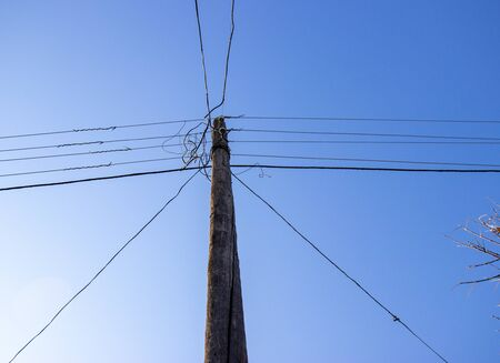 electric pole with wires against a blue sky