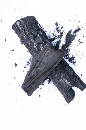 black coal on a white background. a porous black solid consisting of an amorphous form of carbon, obtained as a residue by heating wood, bone or other organic matter in the absence of air.