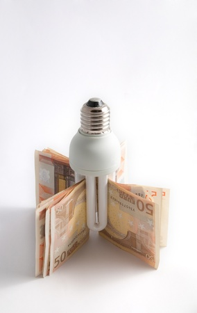 Isolated low consume lamp with 50 euro banknotes on white background photo
