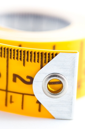 Closed-up of yellow metric tape on white background photo