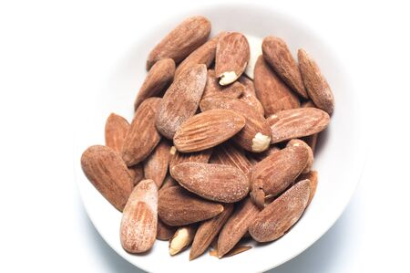 White dish of salted and toasted almonds on a white background photo