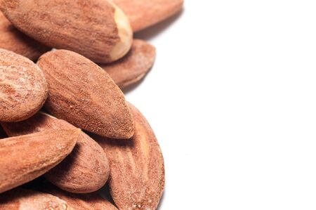 Pile of salted and toasted almonds with copy space on a white background photo