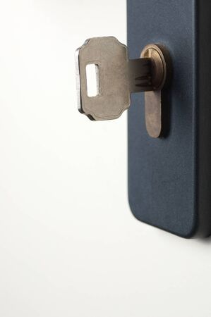 garden key: Locked white door with the key in the keyhole Stock Photo
