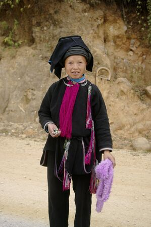 surmounted: This woman is wearing the typical costume of the Dao ethnic black Tien. The trousers and black jacket. The burgundy jabot and cuff typical black cord wrapped surmounted by a truncated inverted pyramid, which is covered with a black cloth. Most women hav