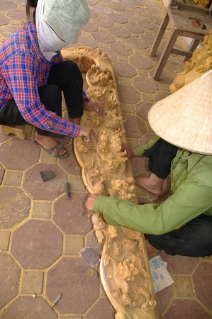 unskilled: Women sanding a sculpture. Women hold most of the unskilled jobs. These women sand it all day carving furniture with sandpaper. As elsewhere in Asia work is squatting on the ground and in the street because of the dust.