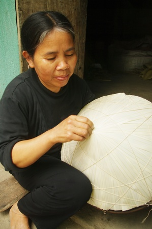 conical hat: woman sewing ethnic kinh un conical hat palm leaves. Editorial