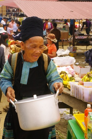 grandma black hmong ethnic group in the region of mai chau. this woman has just bought an aluminum pot to the market of sa linh. Stock Photo - 11128178