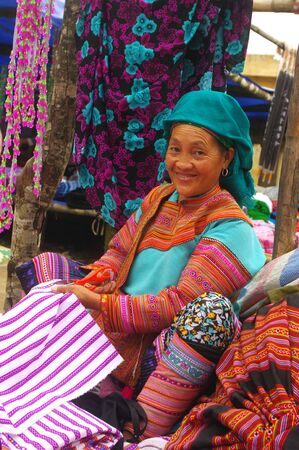 this woman sells hmong floral fabrics traditional designs on the market of sa linh Stock Photo - 11128180