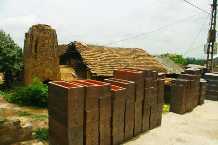 lang: Alley in the village of Phu Lang  This village specializes in the manufacture of urn called  Tieu  in Vietnamese  The houses are installed ovens are too small to store the production  As people store their stock in the village streets
