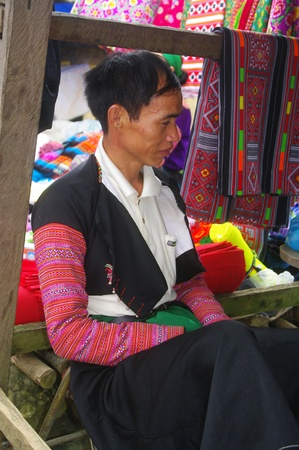 commencing: This man, for the market day has taken its traditional costume  Black pants and jacket  Covered with red sleeves embroidered fabrics  He sits in his stall to sell fabrics
