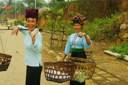 These two women come Khang market  They sold their harvest of vegetables  They puttheir costumes for this special day