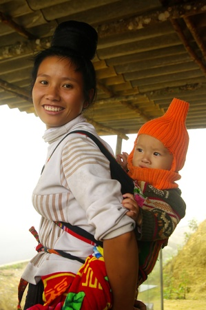 This beautiful young mother of the Thai ethnic group carries its baby in the back  All day the mother will bear the weight of her child even during construction  This young woman to put her hair in a bun right on top of the head as the tradition of his et Stock Photo