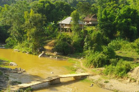 This bamboo footbridge provides access to the tiny hamlet of Thai across the river  The bridge piers are woven bamboo filled with stones