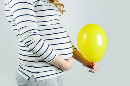 Young beautiful pregnant girl with blond curly hair hugs her belly and holds a yellow balloon, horizontal image