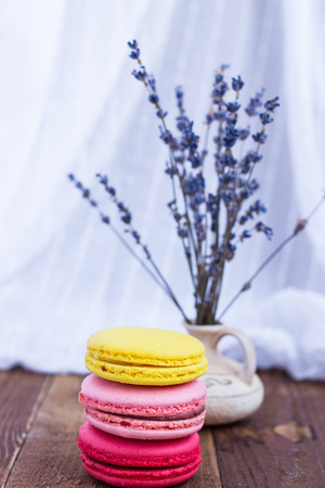 French macaroons and lavender on wooden table. Vintage toned food still life.