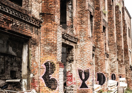 Old messy spooky factory building facade. Abandoned scary house. Stock Photo