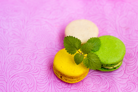 Macaroons fresh colorful close up. French dessert food. Beautiful cakes on pastel background.