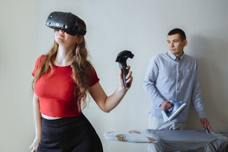 A young girl in virtual reality glasses is playing. Her husband at this time stroking home linen.