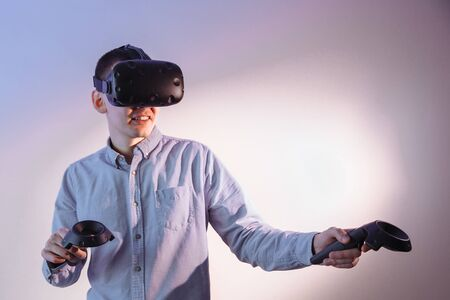 A man in blue jeans with BP glasses and with sticks in his hands is passionate about the 3D game. Stock Photo