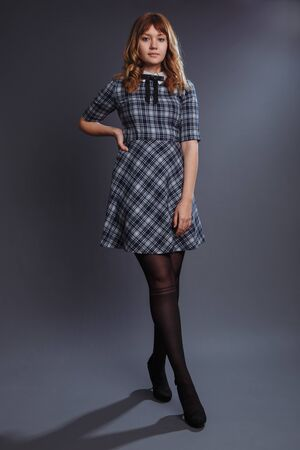 The girl is standing in a confident pose with her legs crossed. The girl in a blue dress in a large ruffle. Tights have a stocking pattern. Studio shot.