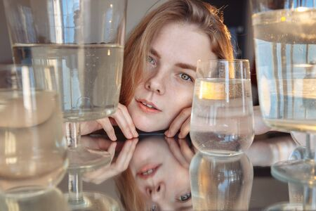 A blonde with cute features looks into the frame. The girl is reflected in the mirror. The girl is surrounded by water containers. the light is falling on the girl from behind.