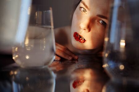 The girls face is illuminated by a beam of light. The ray symbolizes hope. There is a red flower in the girls mouth. The face is reflected in the mirror. There are containers of water around.