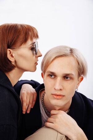 A red-haired girl whispers a secret to a blonde. The girl is wearing sunglasses. Close-up portrait. Young people have identical rings and earrings. The guys gaze is directed to the side
