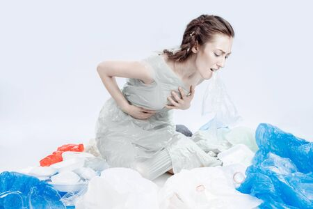 The world is choking on plastic. The girl is sitting on the floor in a plastic bag. Garbage is scattered around the girl. A package protrudes from the girls throat. The girl is sick of garbage.