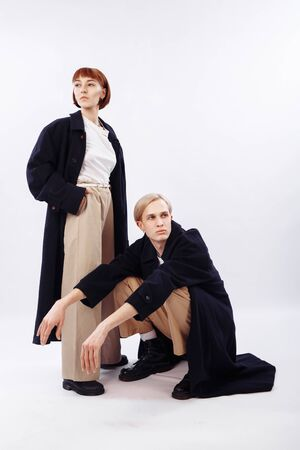 The girl and the guy are dressed the same. The girl stands and looks away. The guy next to me squats and looks the other way. People wear long black raincoats and high-waisted beige trousers.