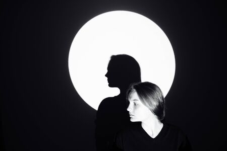 Silhouette of a man against the moon. The girl stands and looks away. Its shadow is in the center of the circle. The rest of the image is dark. There is space for text and entries.