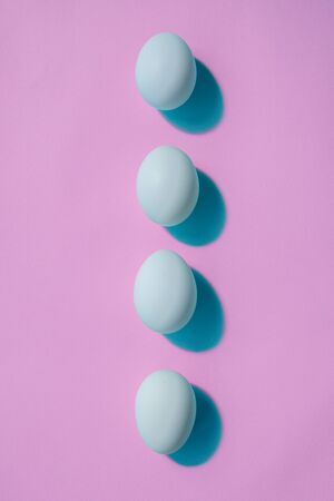 Four blue eggs lie in a row like a spine. The eggs cast a blue shadow. The background of the photo is pink. There is a place for inscriptions.
