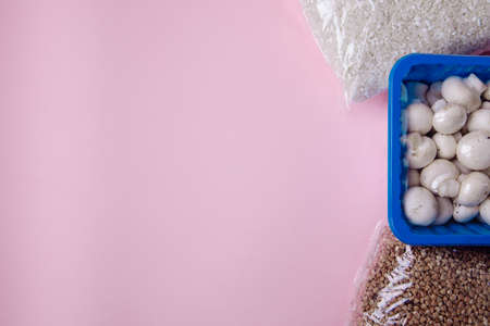 Three universal products: buckwheat. round-grain rice and small mushrooms. The products are in the right corner of the frame. The background is pink. There is an empty space for the text. Stock Photo