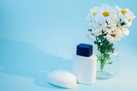 Face soap, aftershave, and a bowl of daisies are on the table. Soap and bottle are white. Vase for daisies transparent background photos blue. There is space for text. High quality photo
