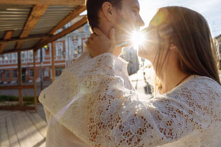 A woman with long hair in a white wedding dress kisses a man. You can see the suns rays through the kiss. The girls hand gently embraces the man. Old town in the background. High quality photo