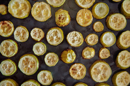 Stewed zucchini cut into rounds on a non-stick protwin. Zucchini of different shapes with traces of heat treatment. zucchini are in the form of flat pattern High quality photo