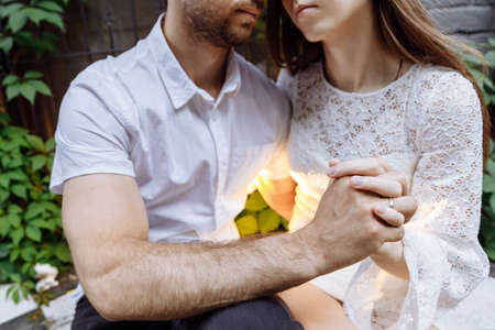 A man and a woman in white clothes embrace. Peoples hands are intertwined. The mans lips are drawn to the womans. The space between them glows. High quality photo