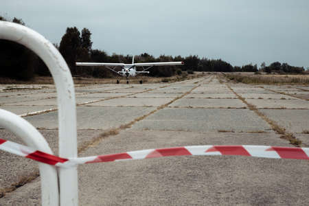 A small white A 27M CIVILIAN plane is parked on the runway. In the foreground, a fencing tape is stretched. The weather is cloudy and rainy. High quality photo