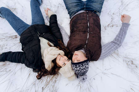 Young happy couple wallowing on white snow after playing snowballs. High quality photo